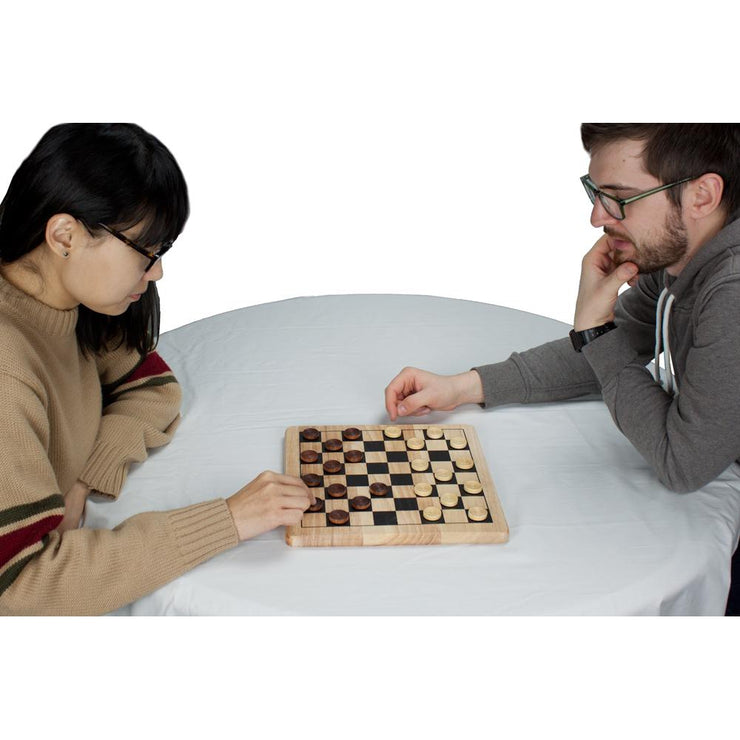 two adults at a table playing checkers