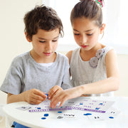 girl and boy playing alphabet bingo on a white table