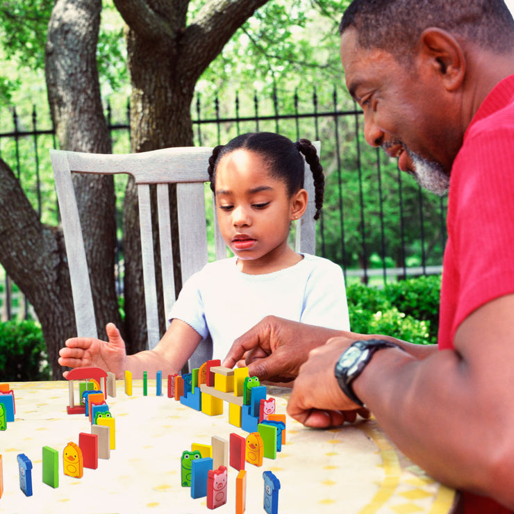 picture of a girl and man playing with the dominoes on a table outside