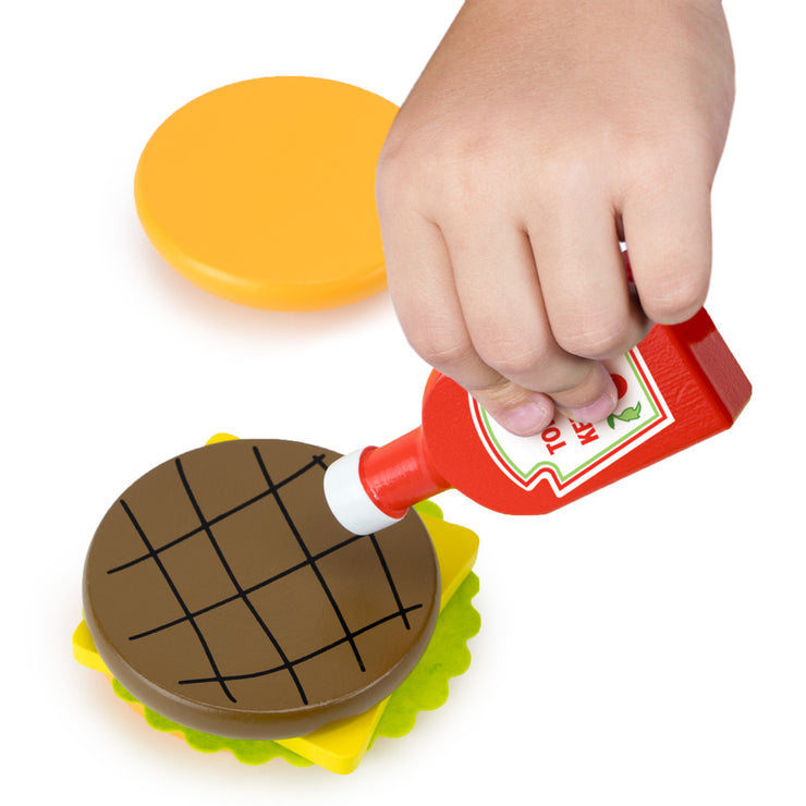 image of a child pretending to add ketchup to a burger - wood eats