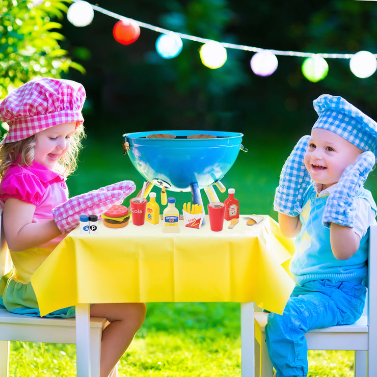 boy and girl playing outside with a barbecue and condiments - wood eats