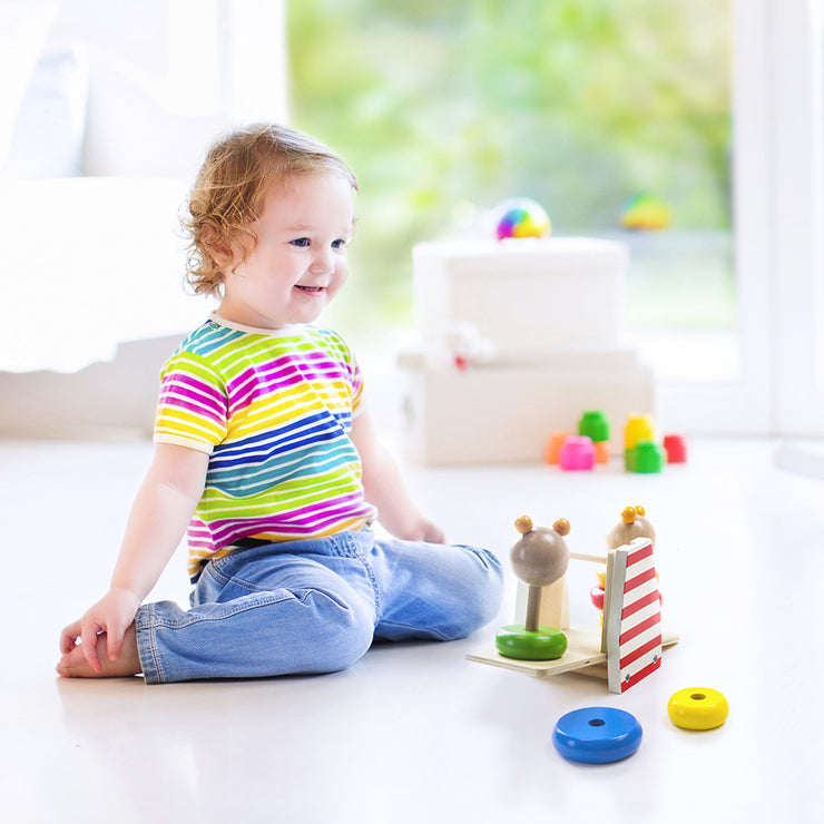 toddler in a striped shirt playing with stem balancing bear see-saw