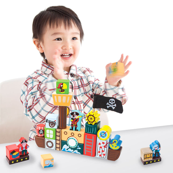 young boy happily building blockbeard's pirate ship at a table