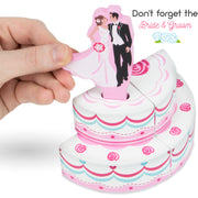 image of a hand placing the bride and groom on top of the wood eats cake