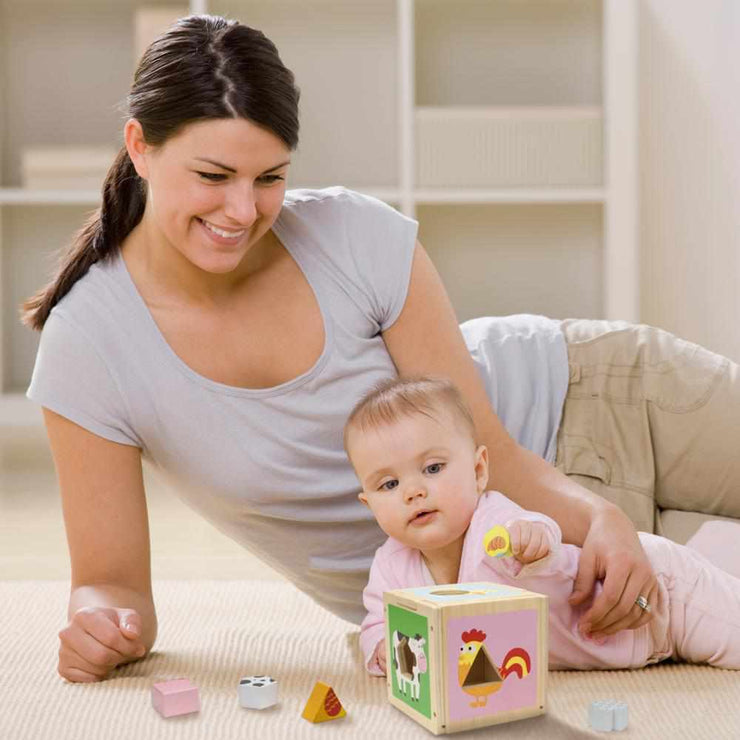 mom and baby playing with a stem sorting cube