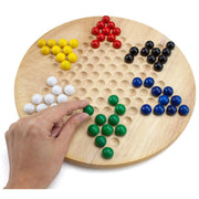 hand placing a green marble on the stem toys chinese checkers board