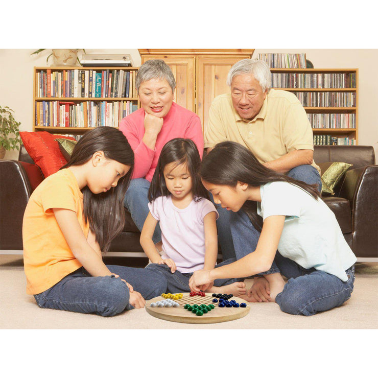 family playing chinese checkers in their lounge