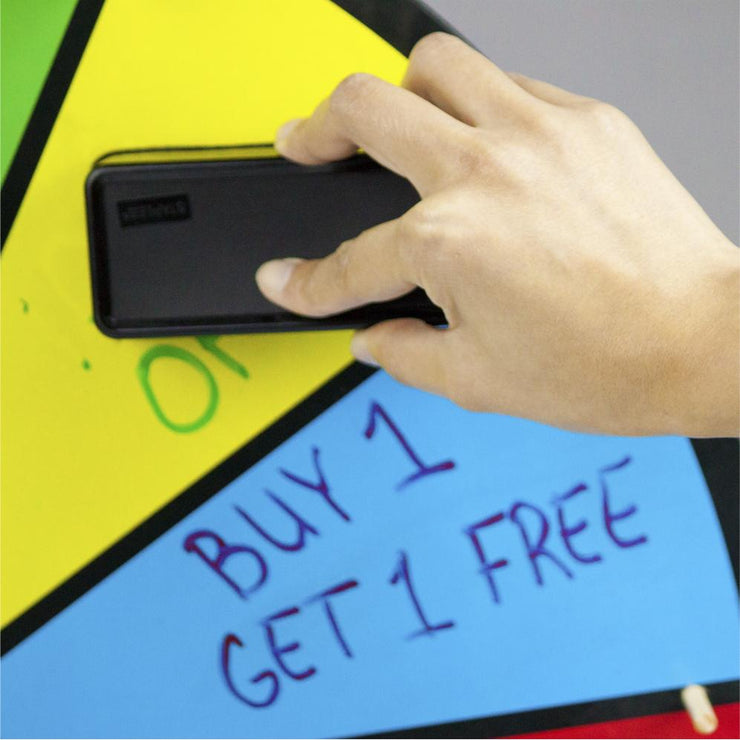 hand erasing writing from the color dry erase prize wheel