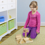 girl in a room playing with her stem toy set of constructables building planks
