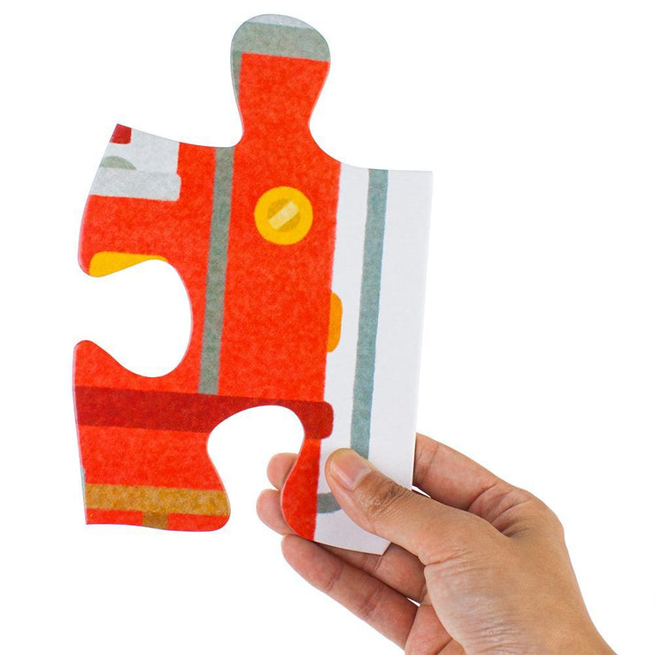 adult hand holding a single stem toy puzzle piece in their hand