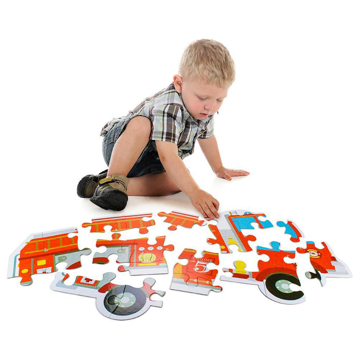 little boy playing with the stem toy fire engine floor puzzle