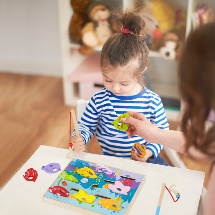 little girl in a striped shirt at a table playing the Let's Go Fishing! Game