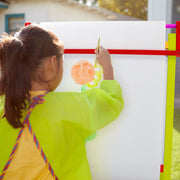 little girt in a yellow apron painting a flower using Little Artists White Easel Paper
