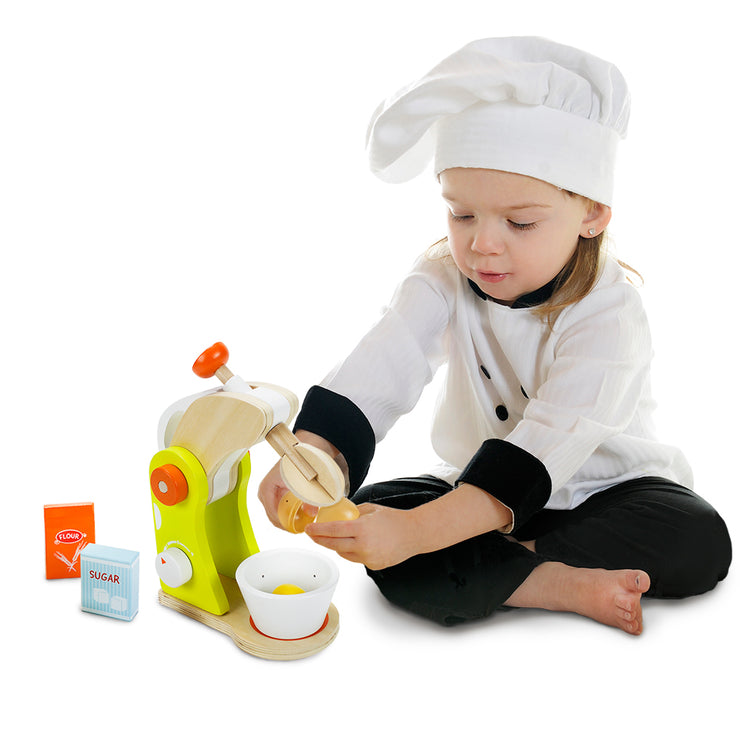 little girl in a chef suit cracking an egg into the wood eats mixer