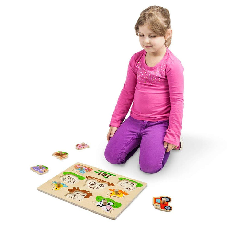 girl in pink playing with Professor Poplar's Wooden Barnyard Peg Puzzle