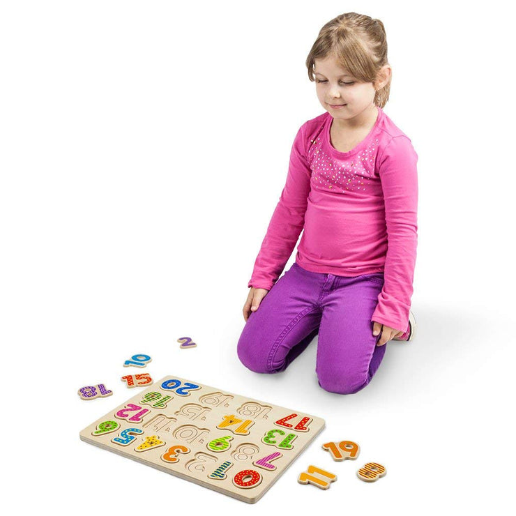 girl in pink playing with the Professor Poplar's Wooden Numbers Puzzle Board