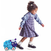 little girl in a checkered dress pulling the Push-n-Pull Swirly Sheep