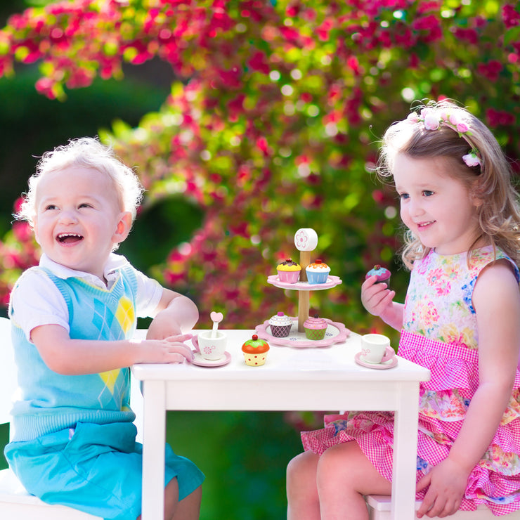 young girl and boy having a tea party in the garden with the wood eats cupcakes