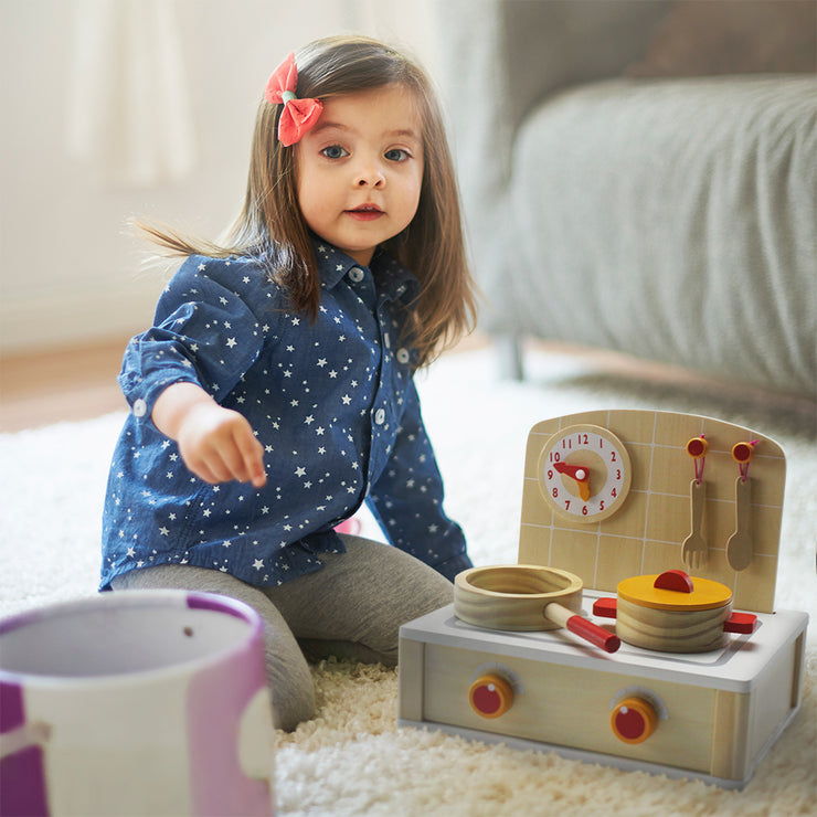little girl on a carpet playing with the cooktop kitchenette set