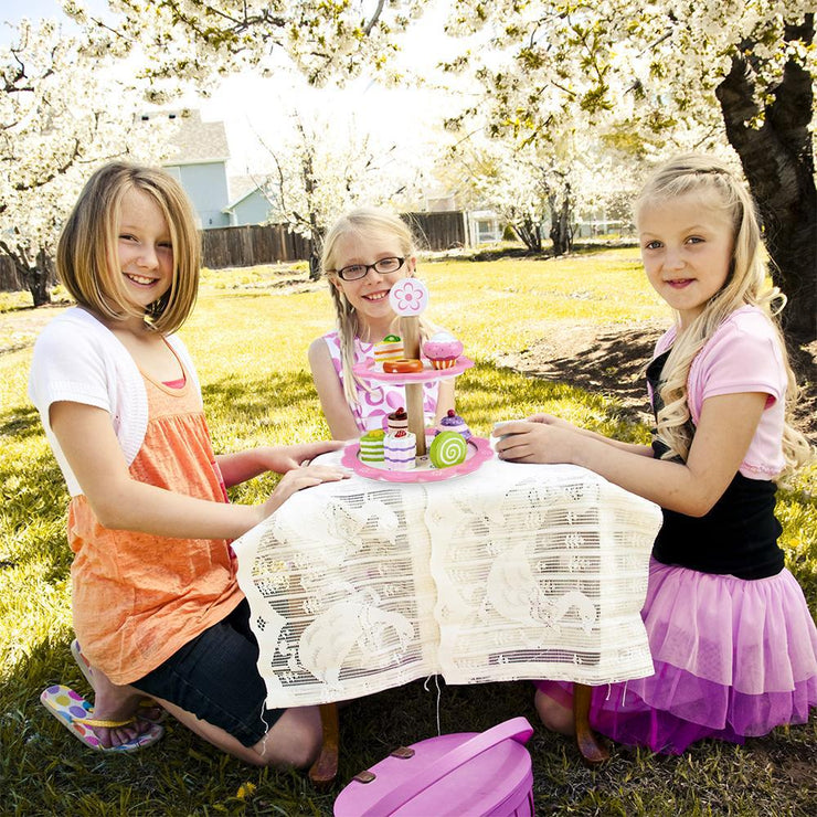 three girls having a tea party outside with their wood eats tea time pastry tower