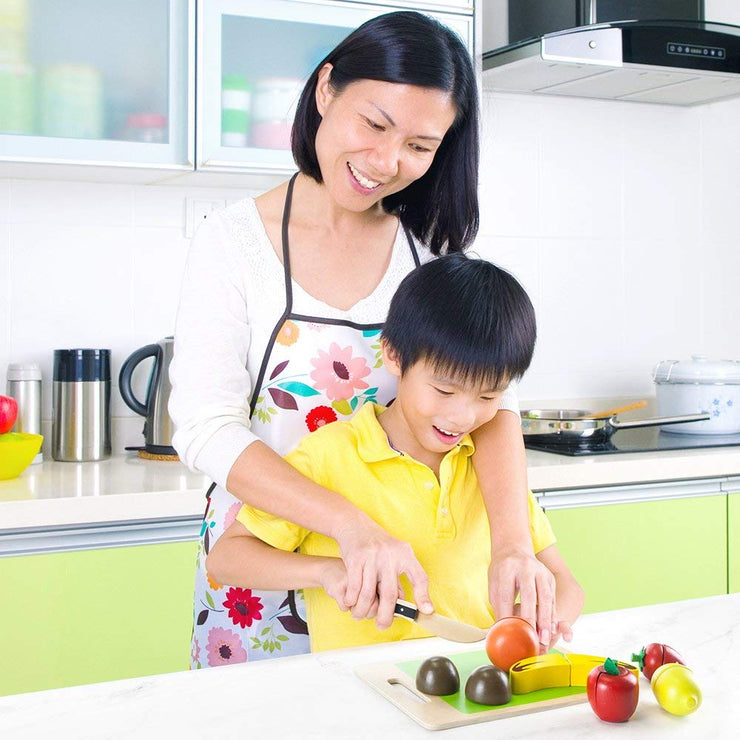 mom and boy playing with wood eats fruit slicers at kitchen bench