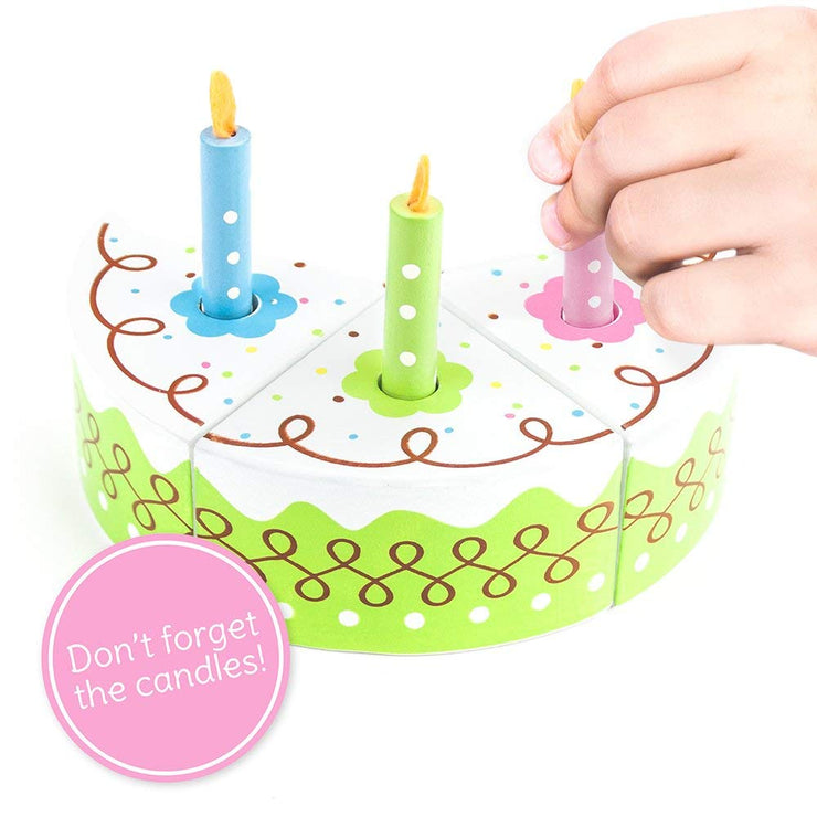 close up of hand placing candle on wood eats birthday cake
