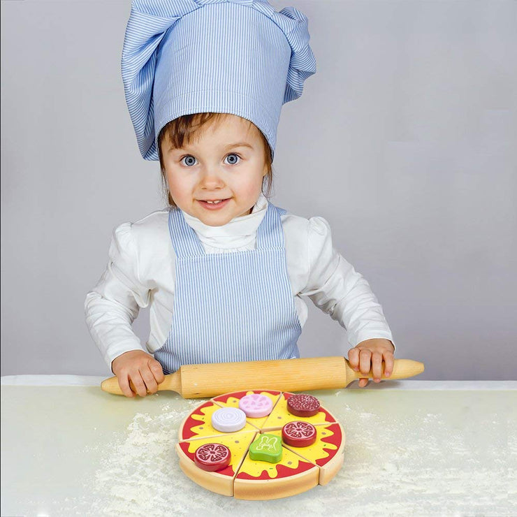 child dressed in a chef suit playing with a rolling pin and pizza