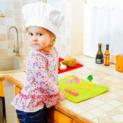 little girl wearing a chef hat preparing for her picnic in the kitchen