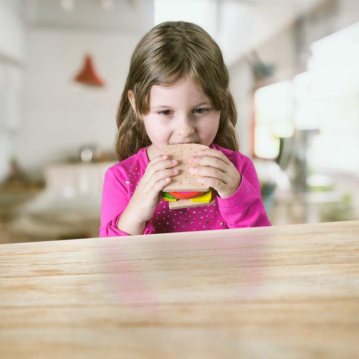 little girl pretending to eat her wood eats sandwich