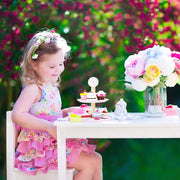 girl sitting outside playing with wood eats cup cakes