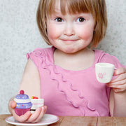 cute girl in pink dress sipping tea and playing with wood eats cup cakes