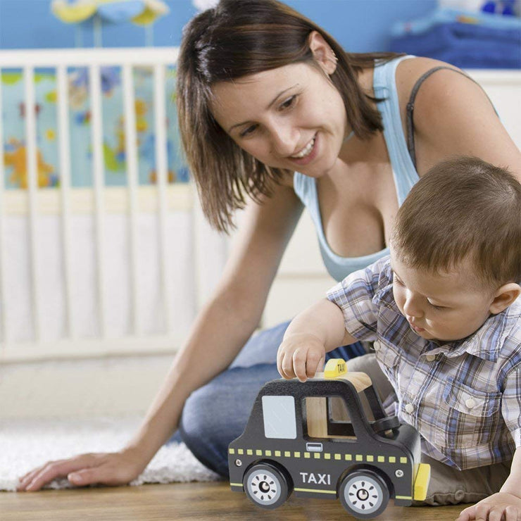 mom and boy playing with black wooden wheels taxi