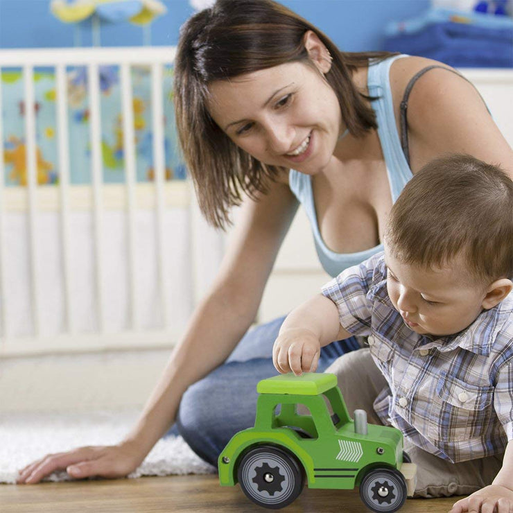 mom and boy playing with wooden wheels green tractor