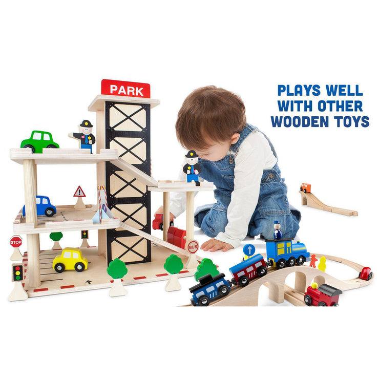 little boy playing with the parking garage text reads plays well with other wooden toys