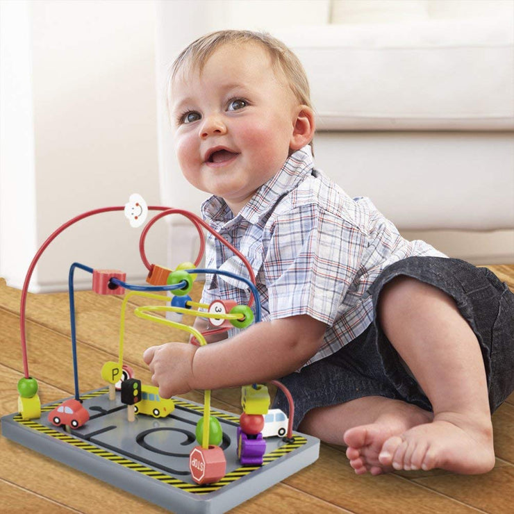 topddler lying down playing with the wooden wonders twisty traffic bead maze