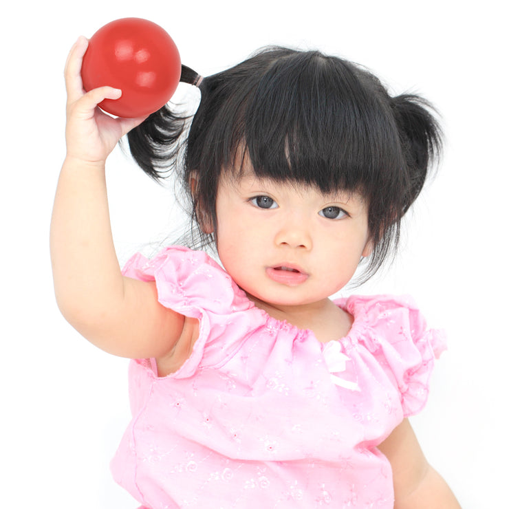 pretty young girl in a pink top holding the red bowling ball