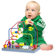 baby in green playing with the wooden wonders twisty traffic bead maze