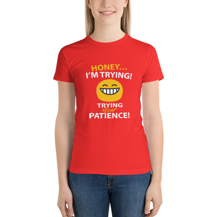 "woman standing in red t-shirt with funny text saying ""honey, im trying... with a petulant face... trying your patience"