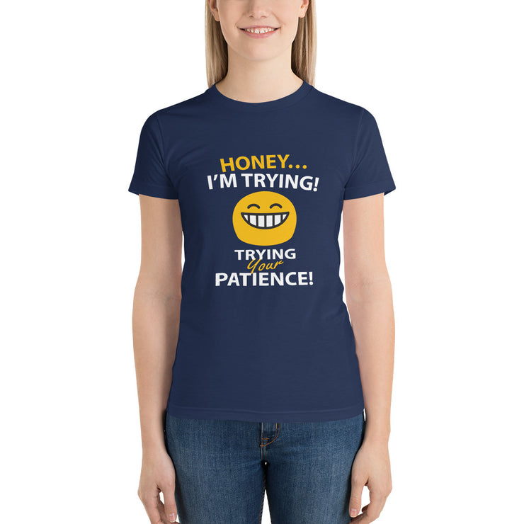 "woman standing in navy blue t-shirt with funny text saying ""honey, im trying... with a petulant face... trying your patience"