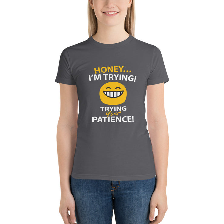 "woman standing in grey t-shirt with funny text saying ""honey, im trying... with a petulant face... trying your patience"