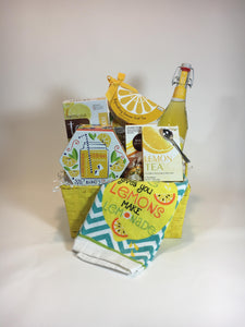 lemonaid themed gourmet.  teas drinks cookies chocolates tuffy chocolates peanut butter filled pretzels keepsake box hand towel all in silverware caddy container