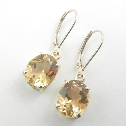 Gold leverback earrings dangle with oval citrines for a custom design.