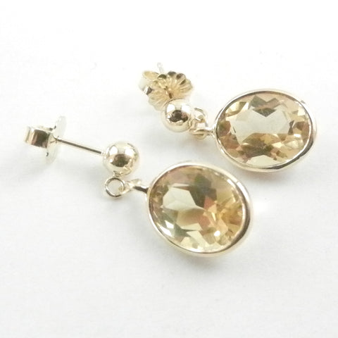 Oval Citrines bezel set in 14 kt yellow gold and dangling from gold ball posts.