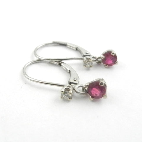 Rubies set in white gold dangle earrings with a leverback are accented with diamonds.