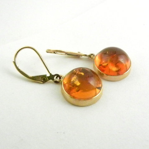 Custom design 14kt yellow gold earrings with round and polished cabochon amber is bezel set and hanging from leverback earrings.