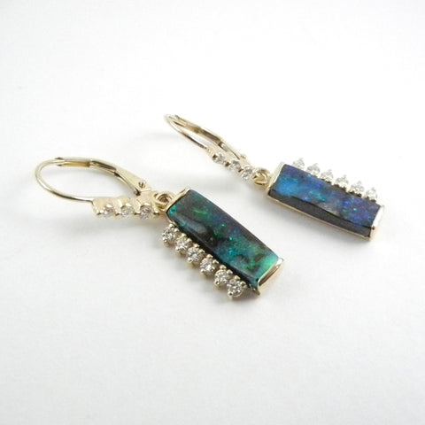 Rectangular black opal dangle earrings with diamonds along one side of each stone. Diamonds accent the leverbacks. Set in 14kt yellow gold.