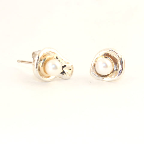 Custom design pearl earrings with silver and gold surrounding a luminous white pearl like a moon.