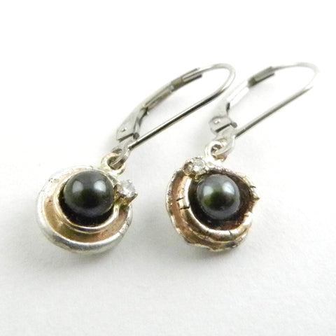 Leverback earrings with tahitian pearls surrounded by an orbit of silver and gold and a twinkling diamond