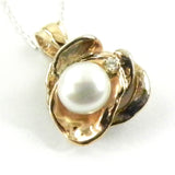 Custom design pearl pendant featuring 14k gold and silver 'puddles' and a twinkling diamond.