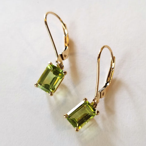 Yellow gold dangle earrings custom made with shimmering emerald cut peridot stones.